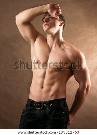 Portrait of a naked muscular man, isolated on beige background