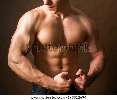 Portrait of a naked muscular man, isolated on brown background
