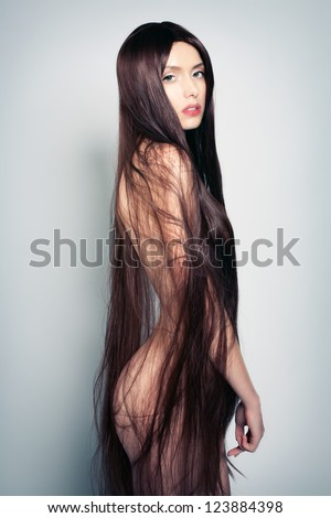 Portrait of a naked young woman with long hair - stock photo