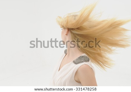 portrait of a natural beautiful girl with long straight blonde hair blowing in the wind. isolated on white background. rear view. - stock photo