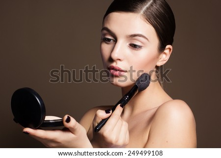 Portrait of a naturally beautiful woman is holding brush and powder that makes skin flawless and perfect - stock photo