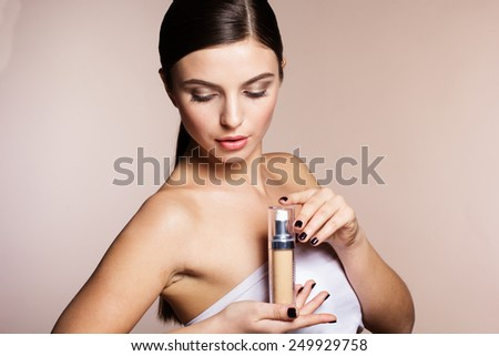 Portrait of a naturally beautiful woman is holding foundation tube for perfect skin tone - stock photo
