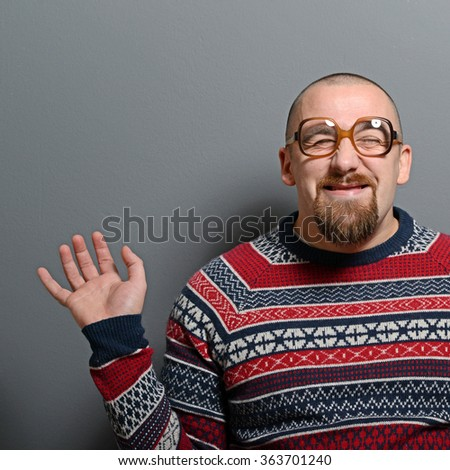 Portrait of a nerd with glasses and retro sweater against gray background - stock photo