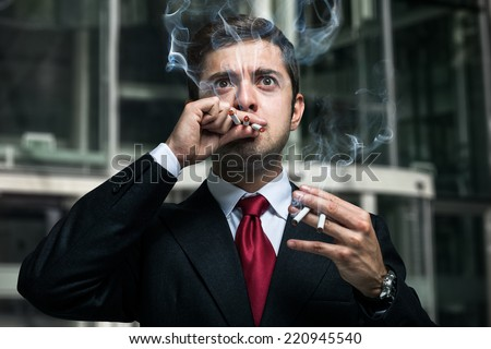 Portrait of a nervous businessman smoking many cigarettes at once - stock photo