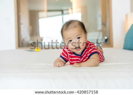 Portrait of a newborn Asian baby on the bed