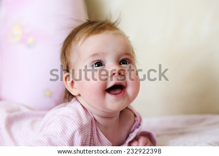 Portrait of a newborn baby girl smiling - stock photo