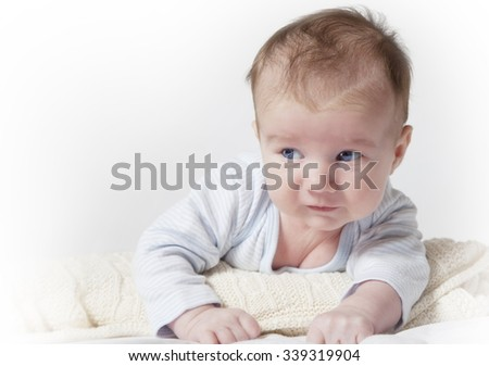 Portrait of a newborn baby lying on his tummy - stock photo