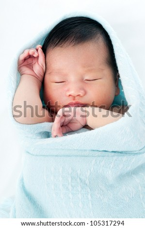 Portrait of a newborn baby wrapped in blanket and sleeping gracefully over white background.