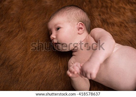 Portrait of a newborn caucasian girl lying on a dark background