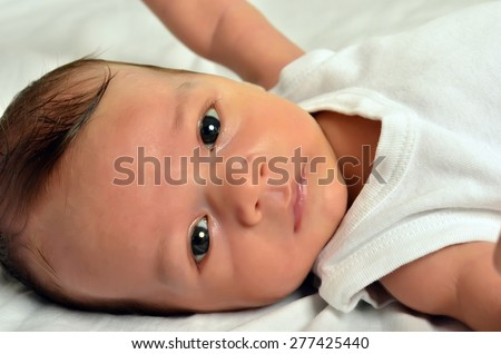 Portrait of a newborn, cute baby looking at you. Adorable little boy relaxing in white sheets after a bath. - stock photo
