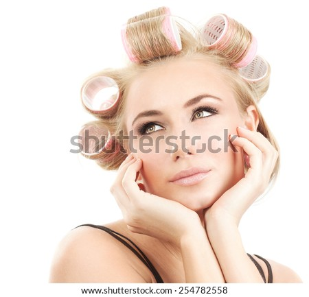 Portrait of a nice blonde model with pink hair rollers, female posing for camera on white background, fashion hairstyle and beauty concept