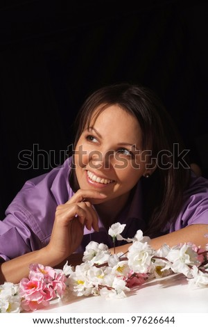 Portrait of a nice charming woman in a shirt in the flower is on a black background