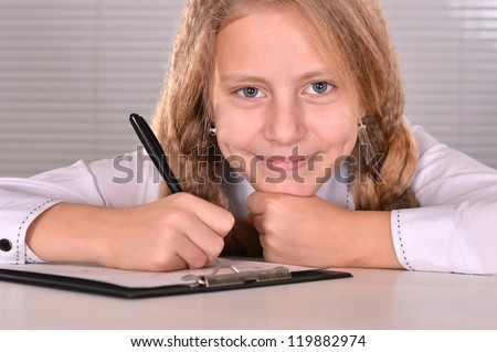 portrait of a nice girl studying at a table on a light background
