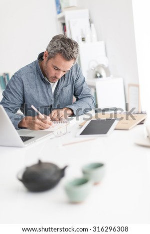 Portrait of a nice grey hair man with beard, working at home on some project, he is sitting at a white table, writing creative ideas on papers with tea in front of him. Focus on the man