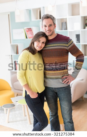 Portrait of a nice middle aged couple standing side by side in their stylish vintage living room.The dark hair woman is leaning her head against the grey hair man shoulder. He is wearing a woolen pull - stock photo
