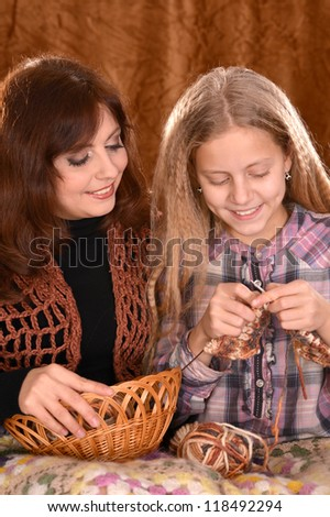 portrait of a nice mom and daughter knitting on a brown