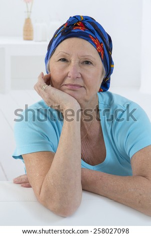 Portrait of a nice senior woman recovering after chemotherapy - focus on her smiling relax attitude - stock photo