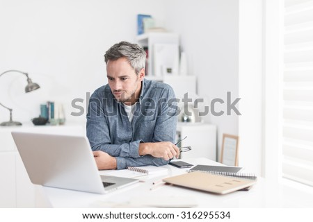 Portrait of a nice smiling grey hair man with beard holding his glasses, working at home on some project, he is sitting at a white table looking at his laptop in front of him. Focus on the man - stock photo