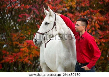 Portrait of a nice white horse and young man on autumn background - stock photo