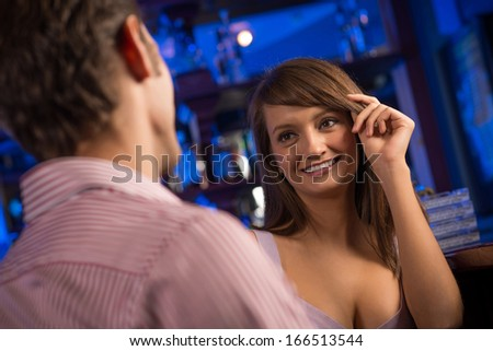 portrait of a nice woman at the bar, talking with a man at the bar date