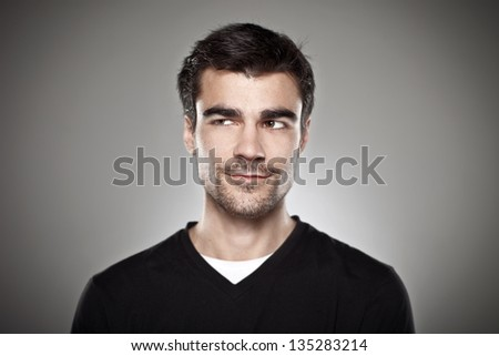 Portrait of a normal boy over grey background / Attractive young man in studio looking askance