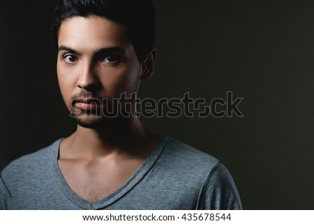 Portrait of a normal boy  over grey background / Attractive young man in studio looking at camera, space for text - stock photo