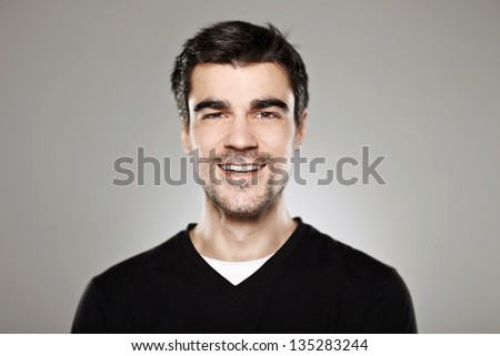 Portrait of a normal boy smiling over grey background / Attractive young man in studio looking at camera - stock photo