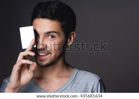 Portrait of a normal boy smiling over grey background / Attractive young man in studio looking at camera, holding a white card for writing the person,  - stock photo