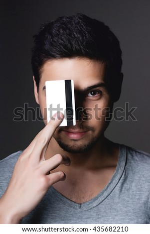 Portrait of a normal boy smiling over grey background / Attractive young man in studio looking at camera, holding credit card in front of face eye - stock photo