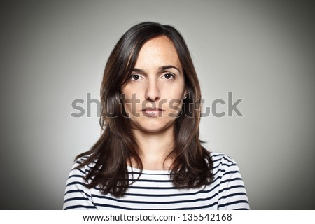 Portrait of a normal girl looking camera. / Beautiful woman portrait over grey background. - stock photo