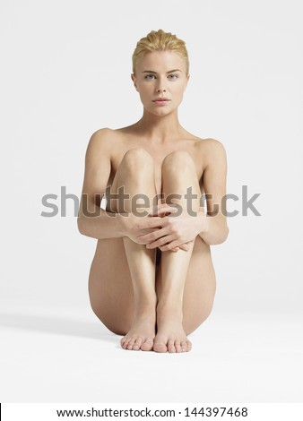 Portrait of a nude young woman sitting with hands on knees against white background - stock photo