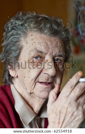 portrait of a old lady smoking a cigar - stock photo