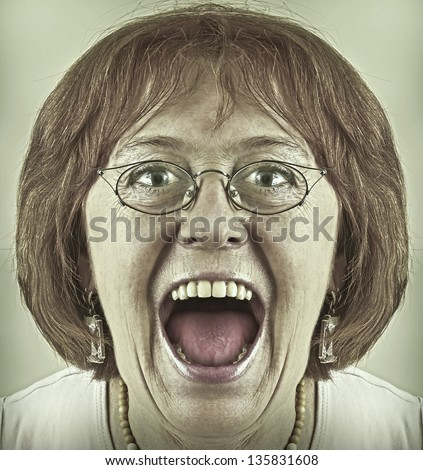 Portrait of a old woman in glasses screaming.