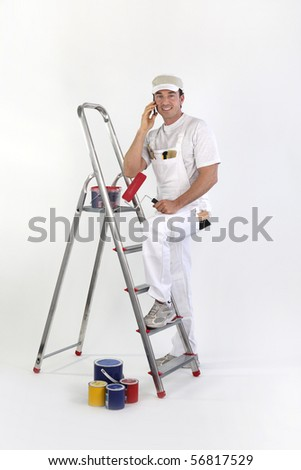 Portrait of a painter leaning on a ladder with a mobile phone - stock photo