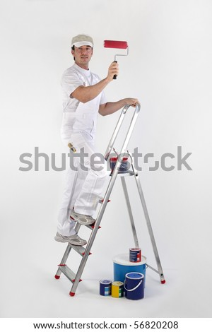 Portrait of a painter on a ladder with a roller brush on white background - stock photo