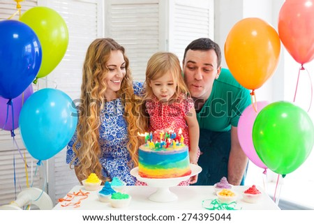 Portrait of a parents celebrating little their daughter's birthday - stock photo