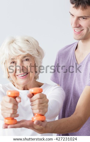 Portrait of a peaceful elderly woman exercising with weights, assisted by a young instructor - stock photo
