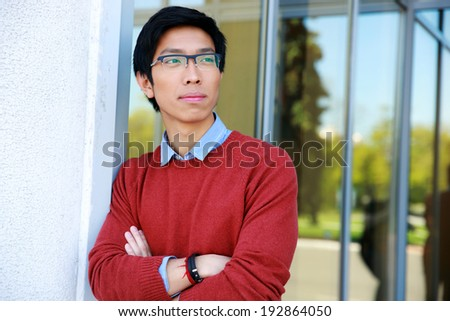 Portrait of a pensive asian man with arms folded - stock photo
