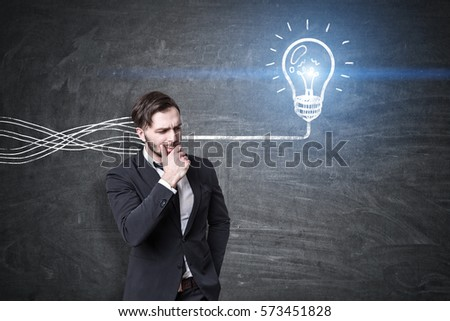 Portrait of a pensive bearded businessman standing near a blackboard with a light bulb sketch on it. Tangled wires enter his head and turn into a single one connected to the bulb.