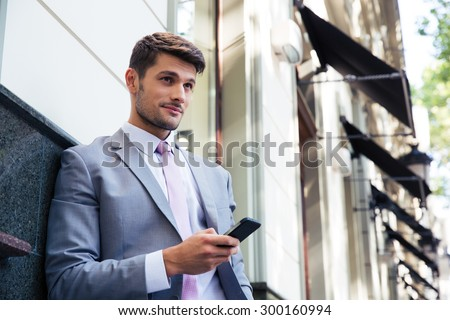 Portrait of a pensive businessman holding smartphone outdoors and looking away - stock photo