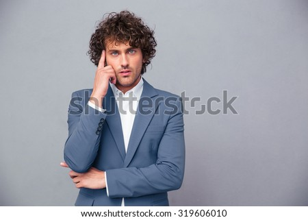 Portrait of a pensive businessman looking at camera over gray background - stock photo