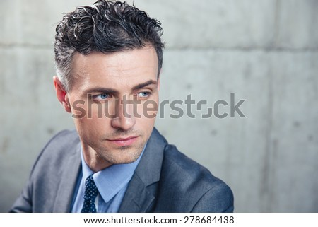 Portrait of a pensive businessman looking away over concrete wall - stock photo