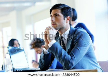 Portrait of a pensive businessman sitting at the table in office - stock photo