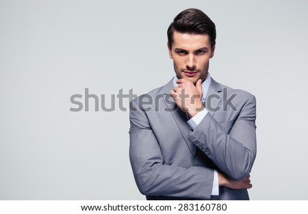 Portrait of a pensive businessman touching his chin over gray background - stock photo