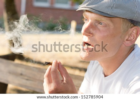 Portrait of a pensive Caucasian middle-aged man smoking a brown cigarette outdoors - stock photo