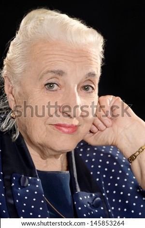 portrait of a���  pensive elderly woman on a black background - stock photo