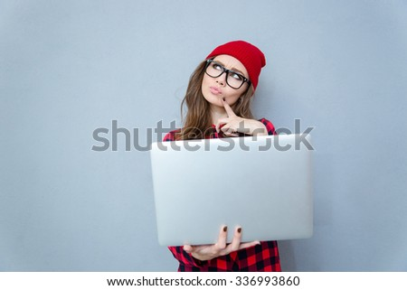Portrait of a pensive hipster woman standing with laptop computer over gray background - stock photo
