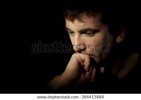 portrait of a pensive man on a dark background - stock photo