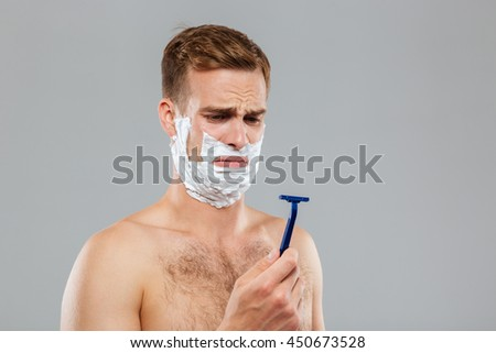 Portrait of a pensive man shaving over gray background - stock photo