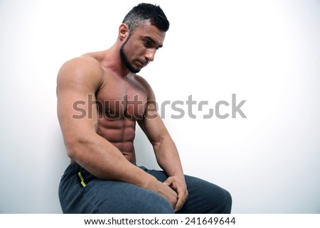Portrait of a pensive muscular man over gray background - stock photo